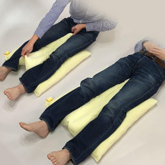 【使用例】下肢を乗せて股関節の内転予防に(下肢の交差予防に)。仙骨部・かかとの除圧に。両端溝に下肢を沿わせて乗せ、真ん中の溝の両端を指で引っ掛けて下肢の間から引き上げます。除圧マットレスに寝ても仙骨部とかかとに圧が集中する理由は、下肢の背部が浮いてすき間があるから。そこの隙間をクッションが埋めて体圧分散します。