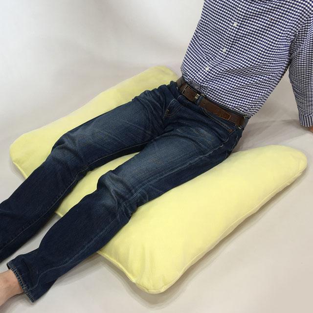 【使用例】ベッド背上げ時の長座位の安定に。坐骨前に凹部を差し込みます。坐骨の前滑りを少なくして骨盤を安定させ、両下肢を保持します。身長178cmの私の場合はこれに加えてかかとの除圧が必要です。ふくらはぎから下を別のクッションなどで支えてかかとを浮かせる必要があります。